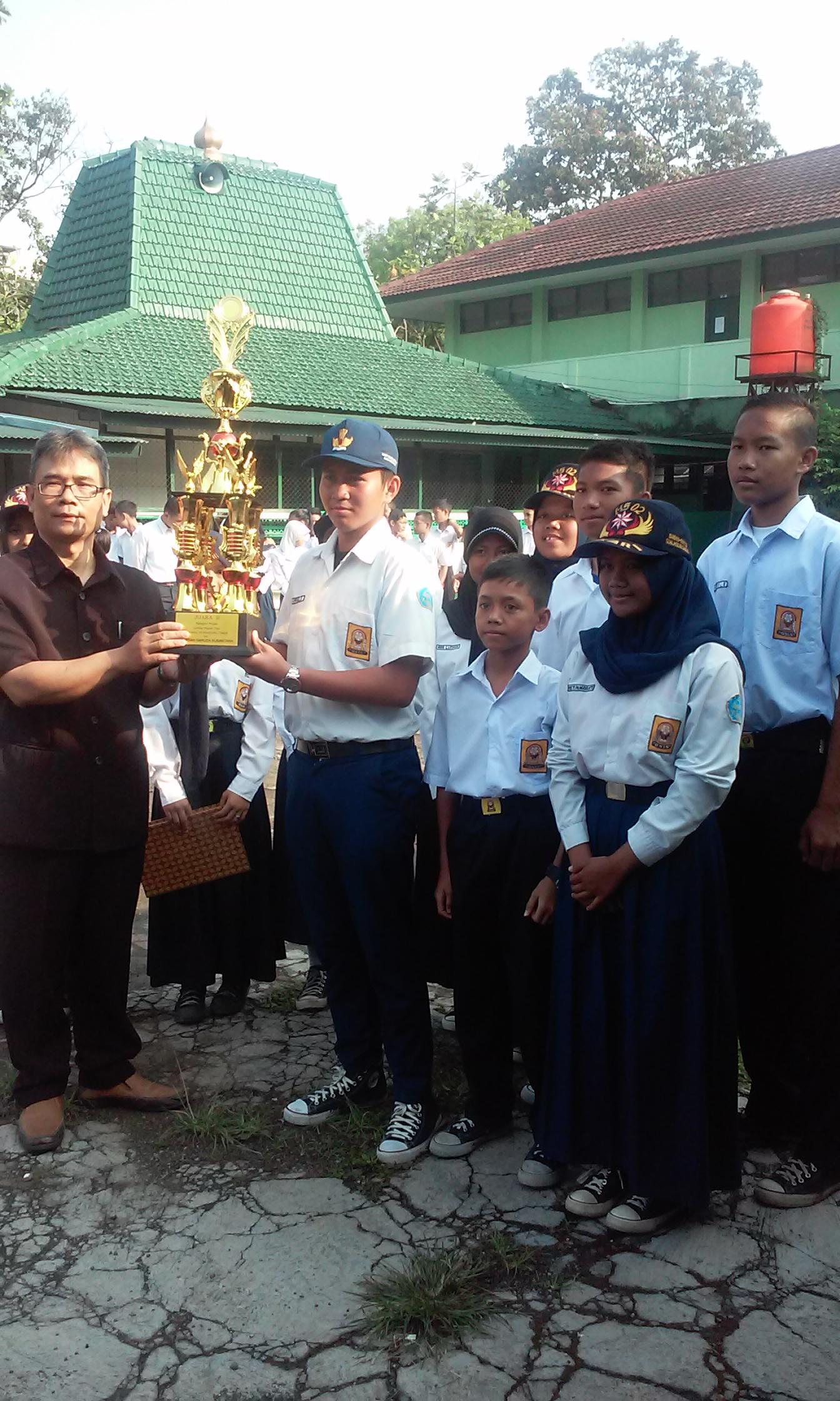 Kepala Sekolah SMP Muslimin 3 saat memberikan piala lke siswa yang berhasil jadi juara